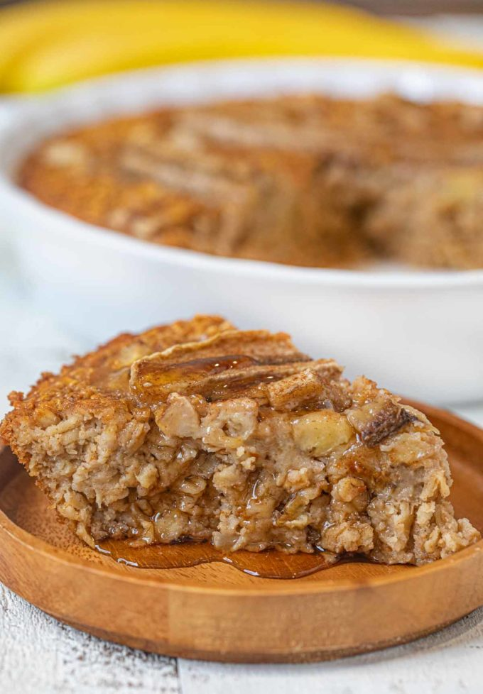 Slice of banana baked oatmeal on small wooden plate with maple syrup