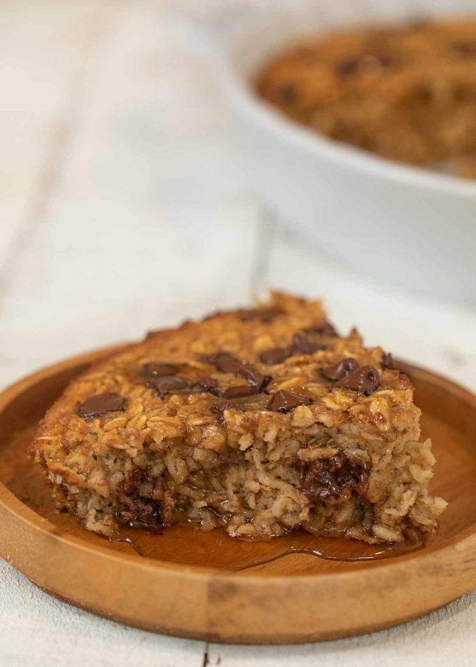 Chocolate Chip Baked Oatmeal slice on plate with maple syrup