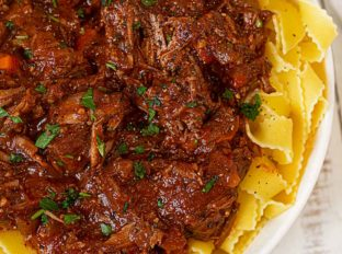 Healthier Beef Ragu over pappardelle pasta in white bowl