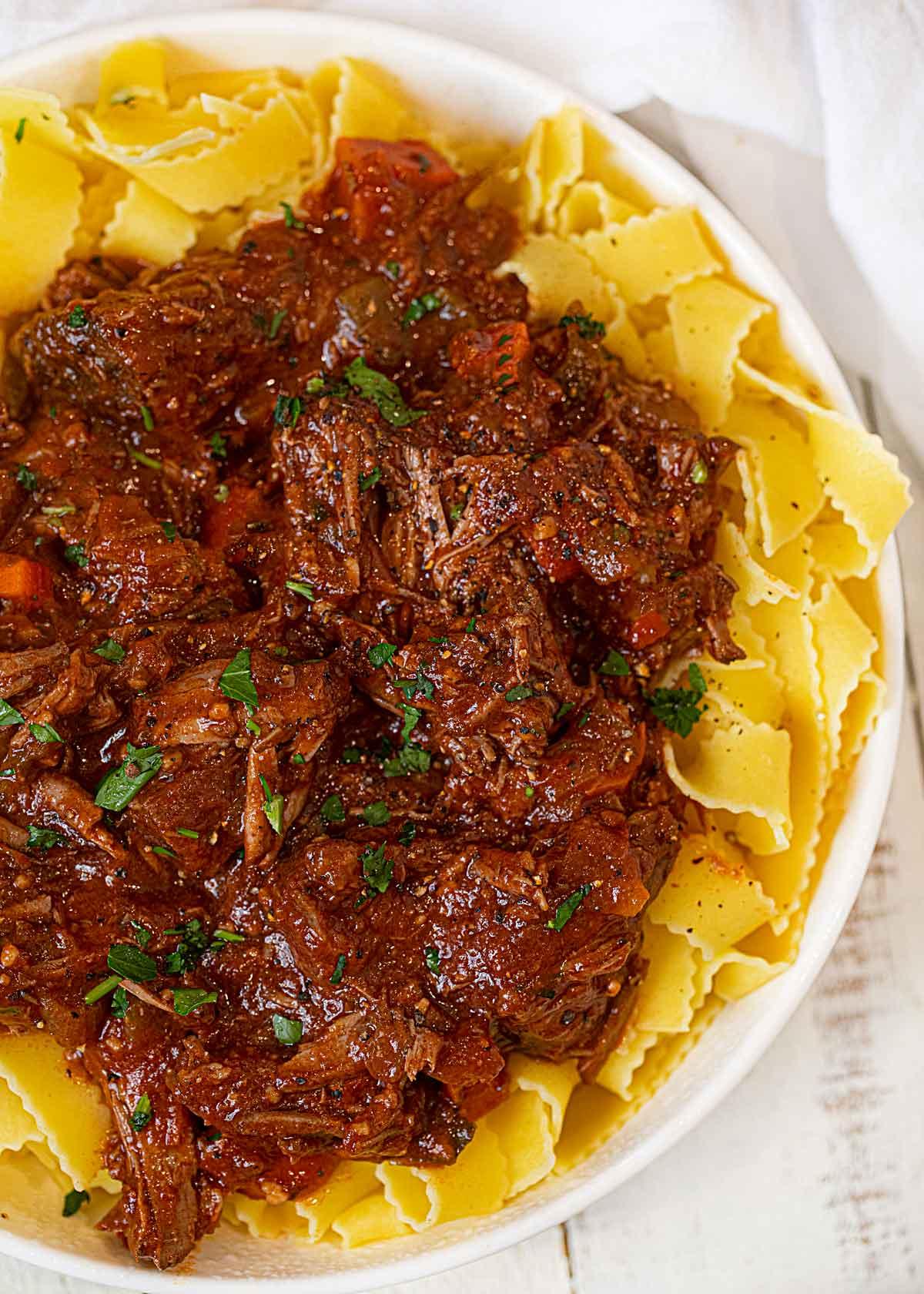 Healthier Beef Ragu over Pasta in white bowl