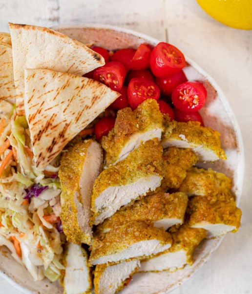 Falafel Crusted Chicken sliced in bowl with slaw and pita bread
