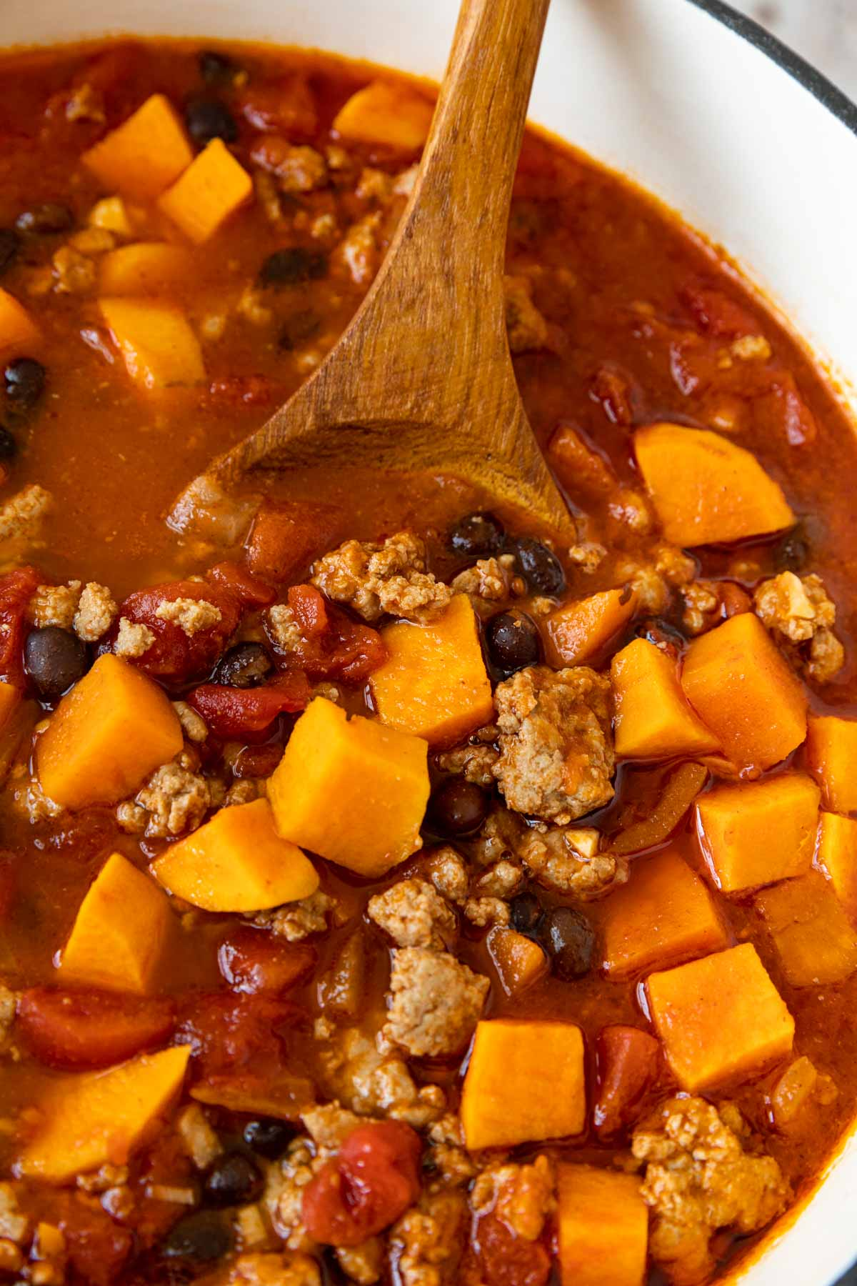 Turkey Sweet Potato Chili in pot with wooden spoon