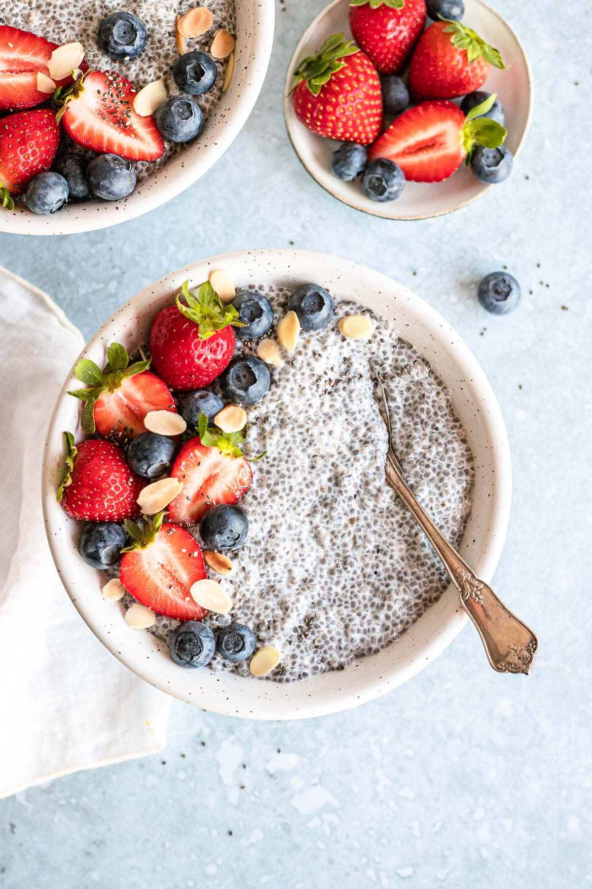 Vanilla Chai Pudding in bowl with berries on top and spoon in the bowl