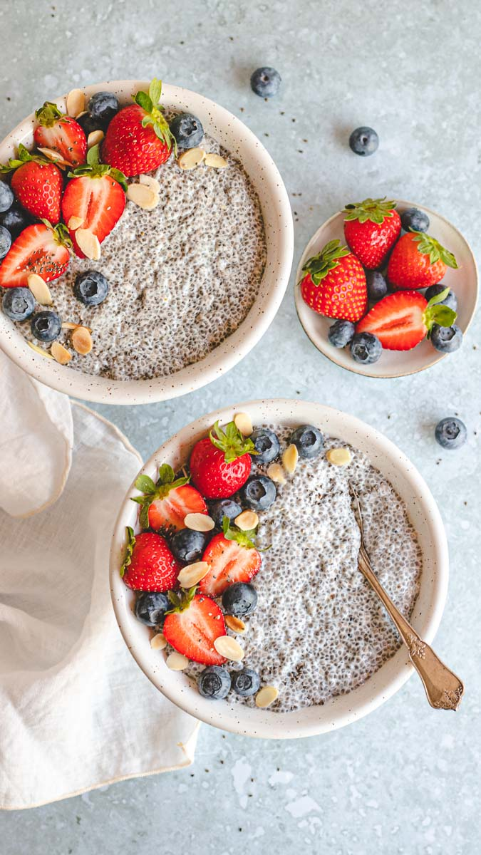 Two bowls of Vanilla Chai Pudding with berries in top and on the side