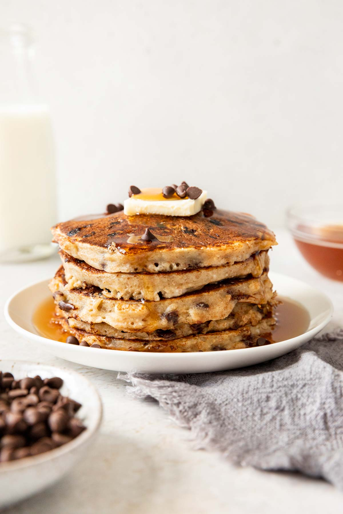 Whole Wheat Chocolate Chip Pancakes on a plate with butter, chips and syrup on top