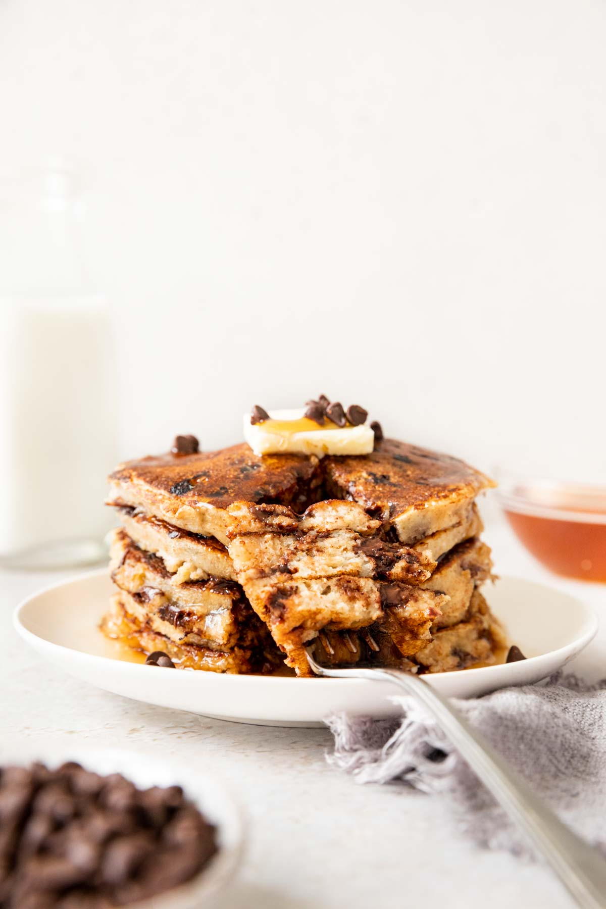 Whole Wheat Chocolate Chip Pancakes up close with butter on top and fork with bite