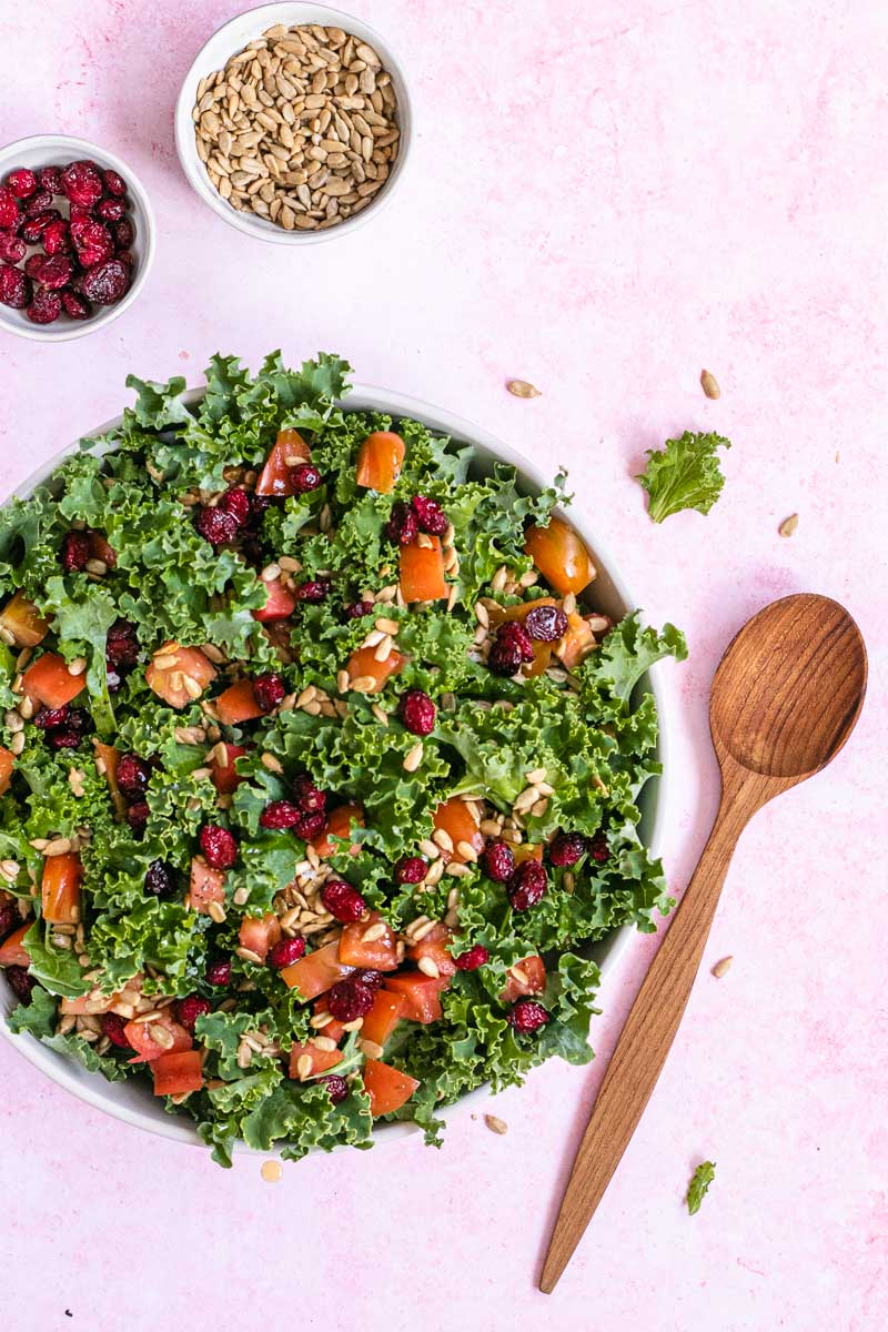 Kale Salad in a bowl with wooden spoon and additional ingredients