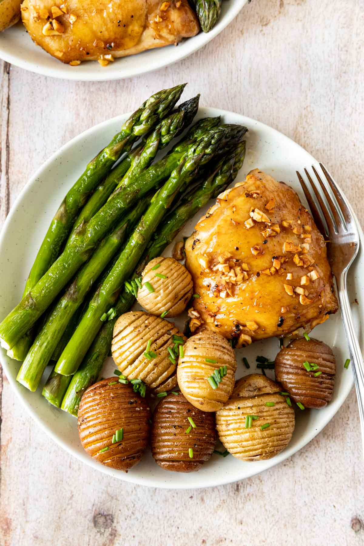 Roasted Garlic Chicken on plate with asparagus and hassel-beck potatoes