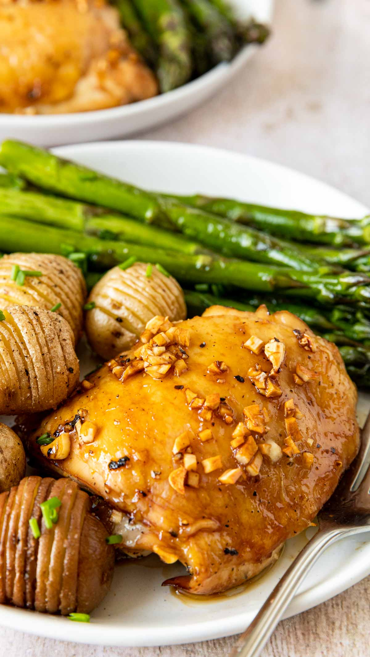 Roasted Garlic Chicken on plate with asparagus and hassel-beck potatoes up close